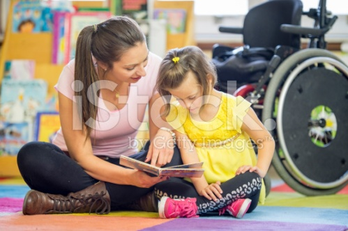 stock-photo-77302265-caregiver-reading-a-book-with-a-mentally-disabled-child